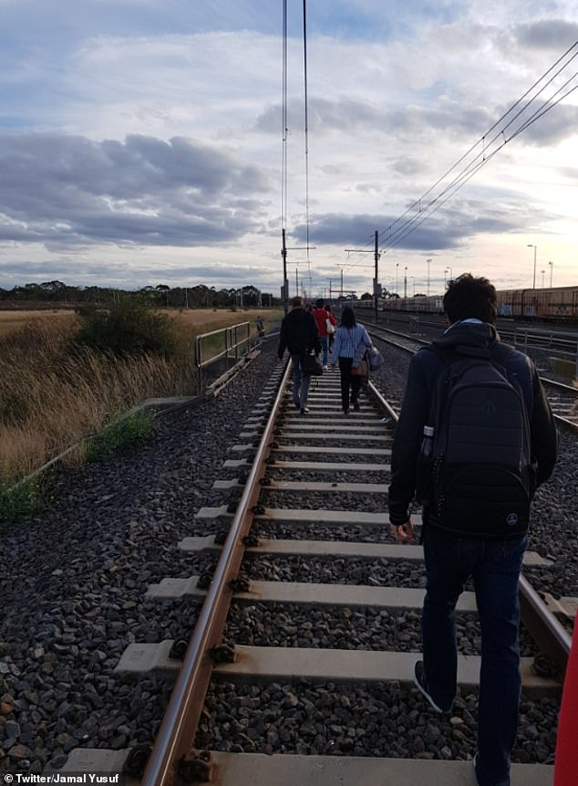 Commuters walked down the train tracks inLaverton on Monday afternoon