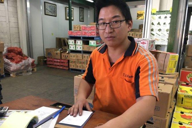 Anh Vinh Nguyen, con trai của ông Frank, đứng bán hàng cho gian hàng của cha ở khu chợ Sydney Markets - Ảnh: ABC